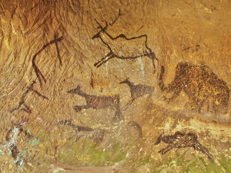 Abstract children art in sandstone cave. Black carbon paint of human hunting on sandstone wall. Copy of prehistoric picture royalty free stock images