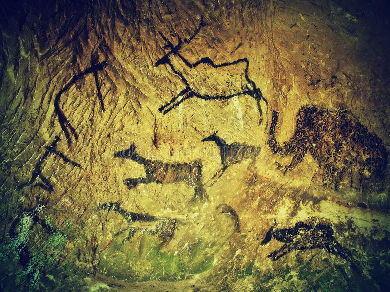 Abstract children art in sandstone cave. Black carbon paint of human hunting on sandstone wall, copy of prehistoric picture. Abstract art in sandstone cave stock images
