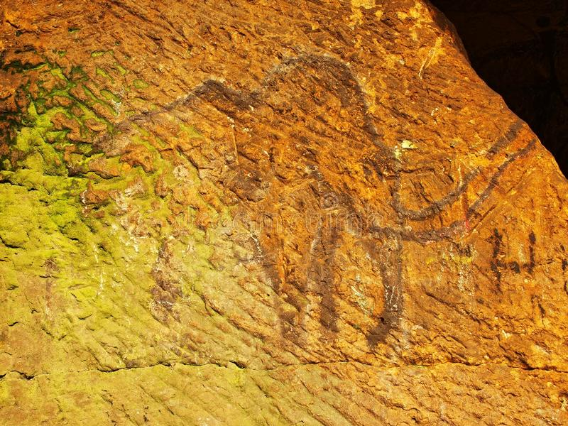 Abstract children art in sandstone cave. Black carbon paint of mammoth on sandstone wall. Copy of prehistoric picture royalty free stock photos