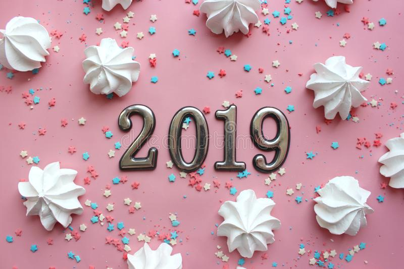 Figures 2019 on a pink background surrounded by colorful confetti and white meringue. royalty free stock images