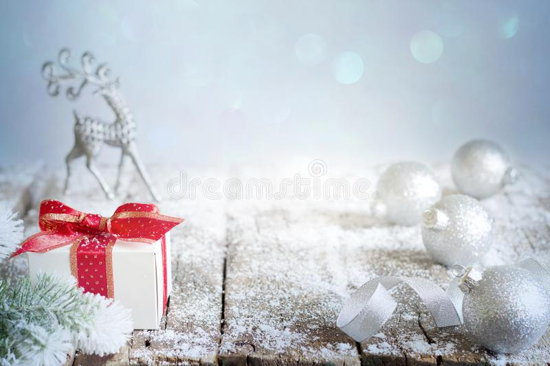 Abstract christmas background with silver baubles gift and reindeer on snow. And bokeh stock images