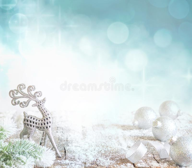 Abstract christmas background with silver baubles and reindeer on snow. And bokeh stock images