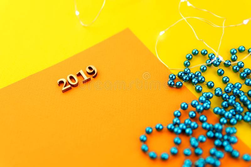 Abstract Christmas background. On a yellow background with blue beads is a card with numbers 2019. Cropped shot, close-up, horizontal, blurred, free space for stock image