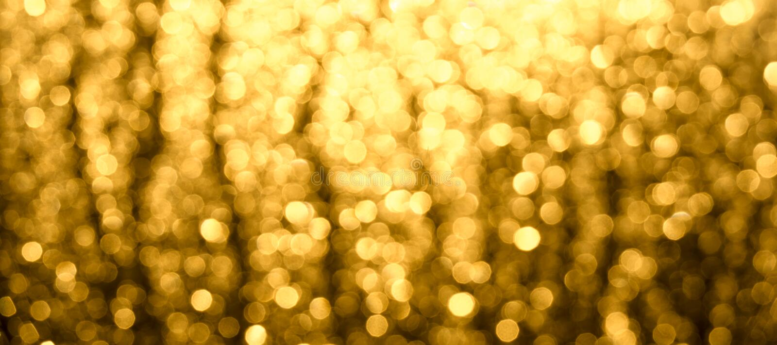 Abstract Christmas blurred background. A Golden-brown glow of Bokeh. Horizontal shot of abstract blurred background. The Golden-brown glow of Bokeh stock images