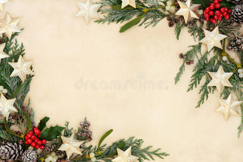 Abstract Christmas Border. Christmas abstract background border with gold star decorations, holly, mistletoe and snow covered cedar cypress on parchment paper royalty free stock photography