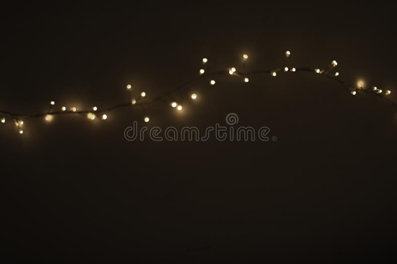 Abstract Christmas lights on black background. Defocused Glow. Ing light bulb garland, copyspace stock photography