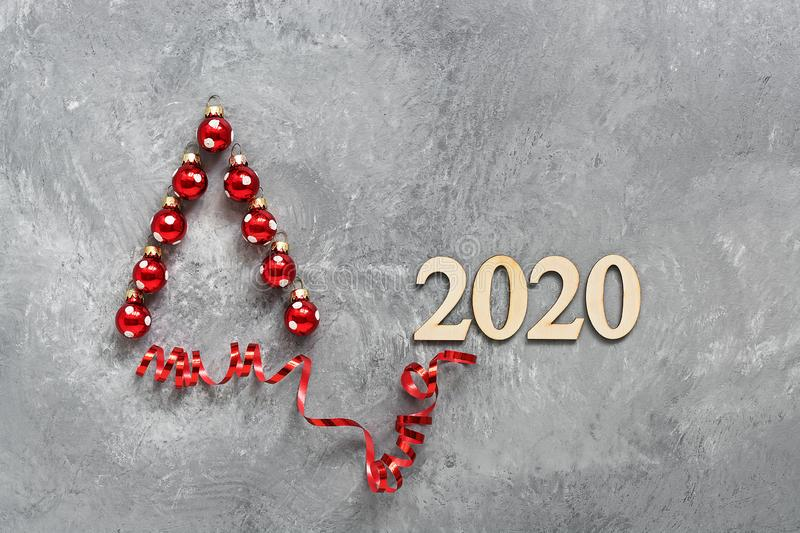 Abstract Christmas tree made from red Christmas balls and ribbons on a gray concrete rustic background. New Year 2020 wooden stock photo