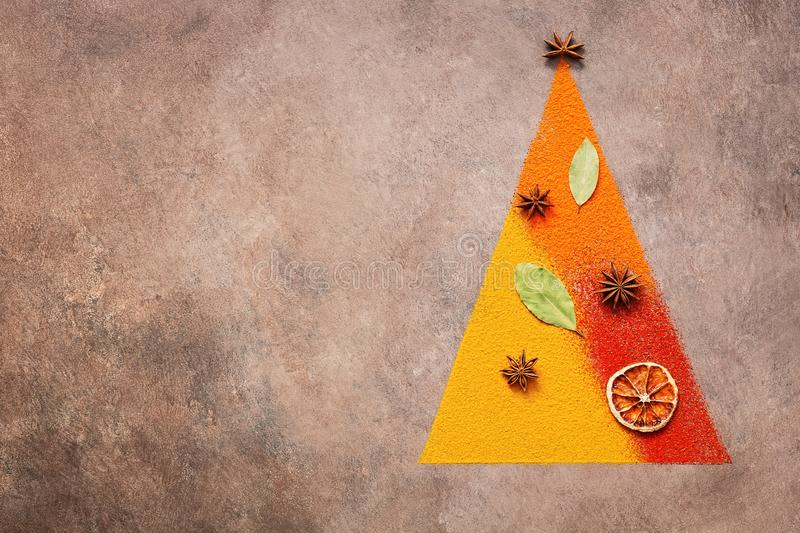 Abstract christmas tree made of spices on dark rustic background. Holiday concept. View from above stock images