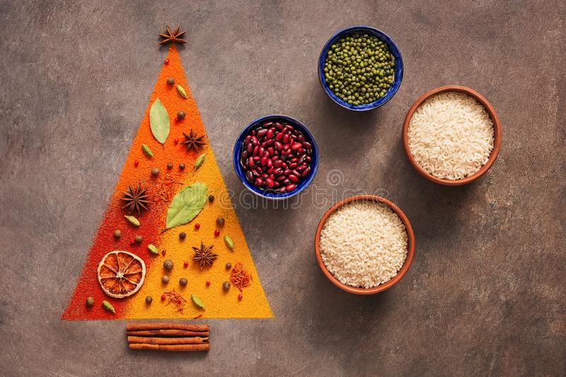 Abstract christmas tree made from a variety of spice and bowl with beans and rice on a dark brown rustic background. Top view, stock images
