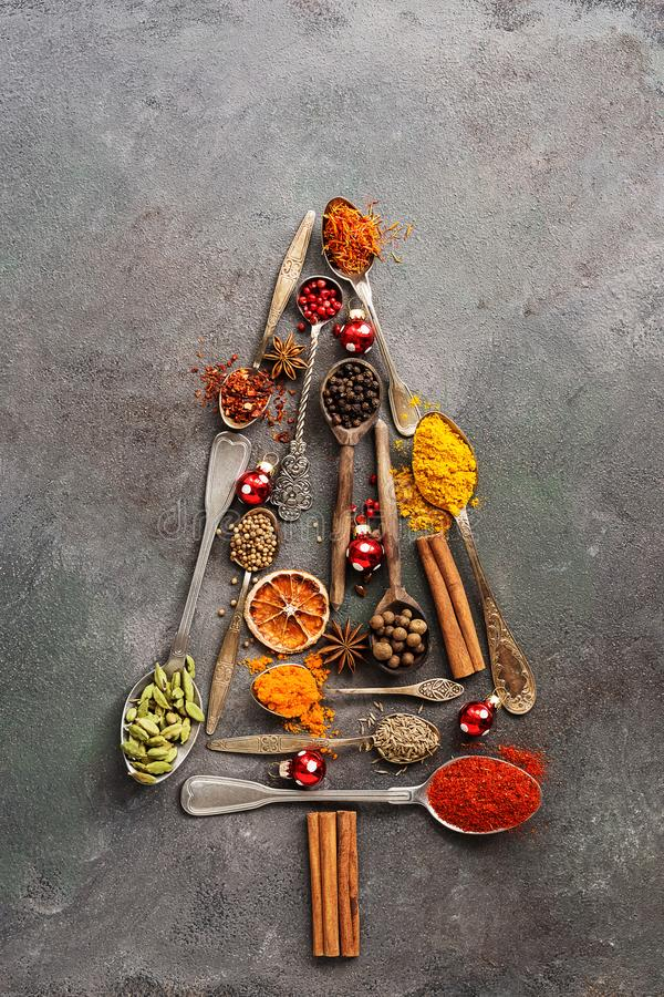 Abstract Christmas tree made of various spices in spoons on a dark rustic background. Top view, flat lay, copy space royalty free stock photos