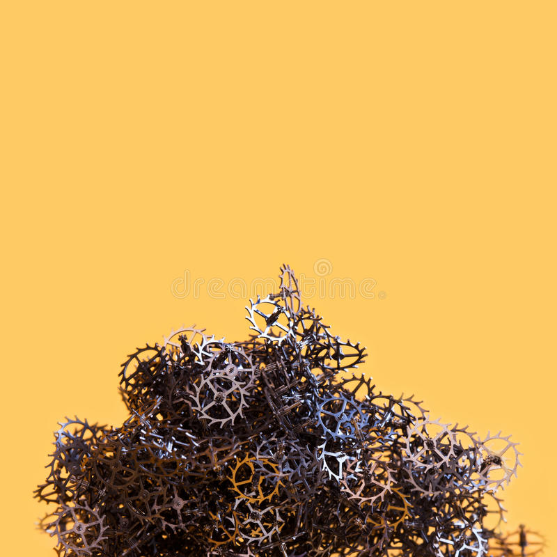 Abstract cogs gears mountain on yellow background. Mechanical industrial still life conceptual photo. Thousand metallic royalty free stock photography