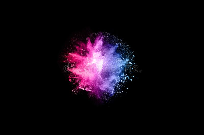 Abstract colored dust explosion on a black background. Abstract powder splatted background,Freeze motion of color powder exploding/throwing color powder stock photography