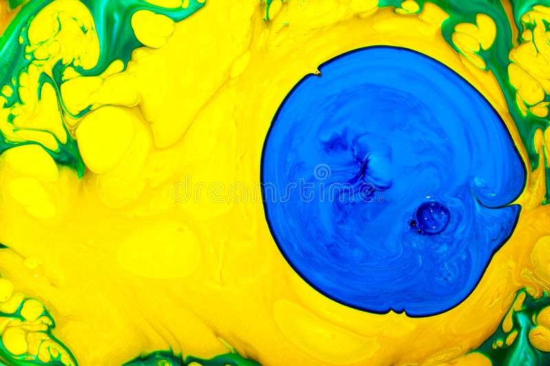 Abstract yellow multicolored background green blue view macro paint acrylic underwater ultra drop blob drip. Abstract colored yellow and blue acrylic paints royalty free stock image