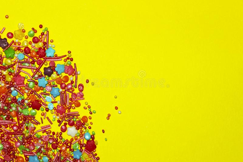 Many Multicolored Candy Sweets On Yellow Background. royalty free stock photography