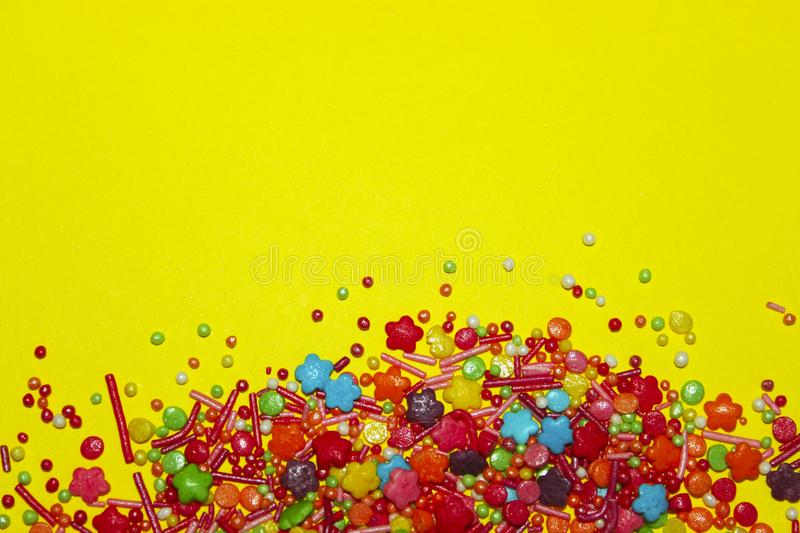 Many Multicolored Candy Sweets On Yellow Background. stock photos