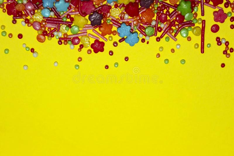Many Multicolored Candy Sweets On Yellow Background. stock image