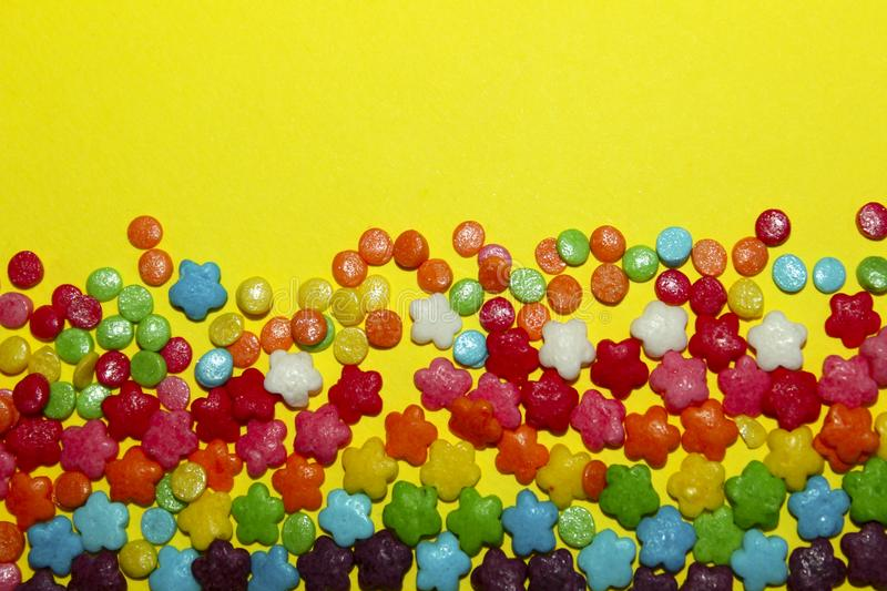 A Lot Of Multicolored Candy Sweets On Yellow Background. royalty free stock photo