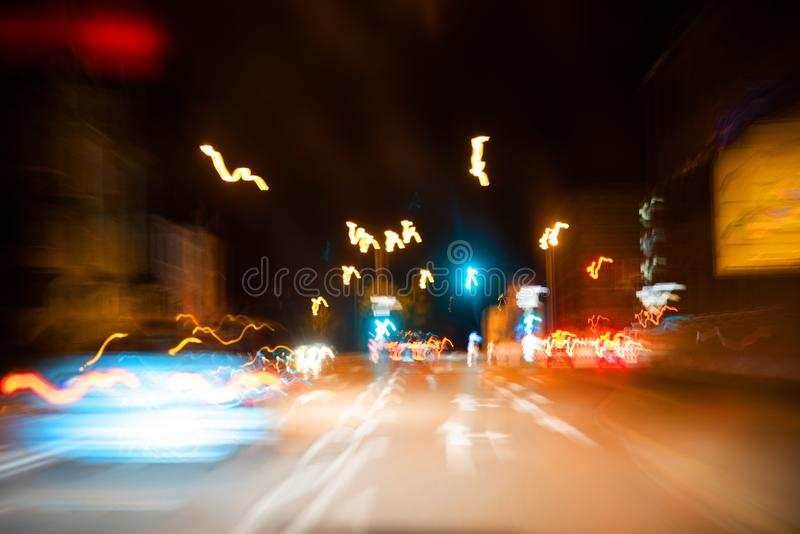 Abstract colorful background, car at speed, light traffic lights, pointers and signs, nightlife in metropolis. Abstract colorful background, car at speed, light stock photo