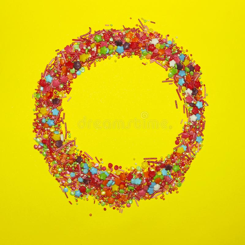 A Lot Of Multicolored Candy Sweets On Yellow Background. stock images