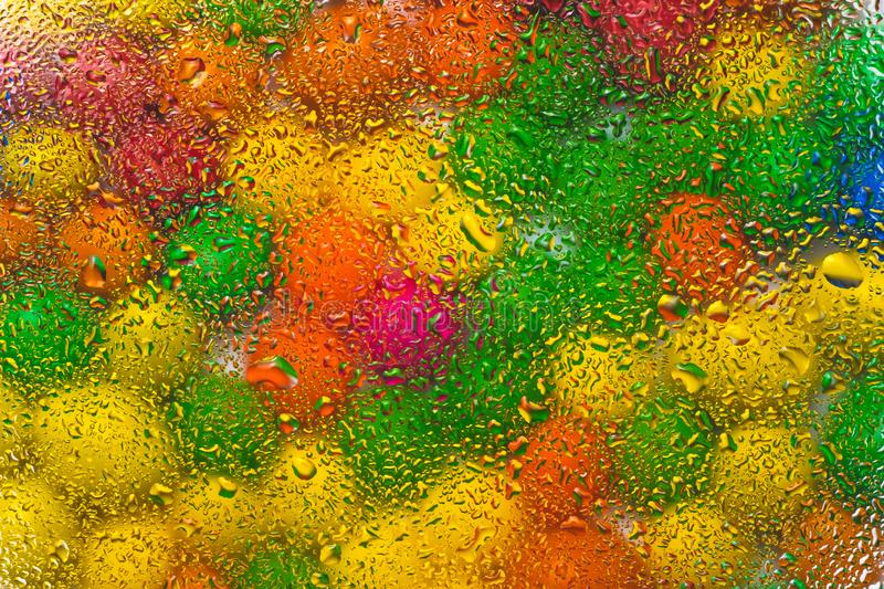 Abstract colorful background with drops of water on multicolor glass. The circles of color of rainbow on wet glass. Creative desig stock photos