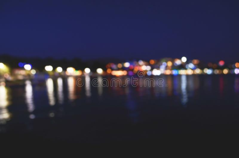 Abstract colorful bokeh effect city lights reflected over night water outdoor background. Image royalty free stock photos