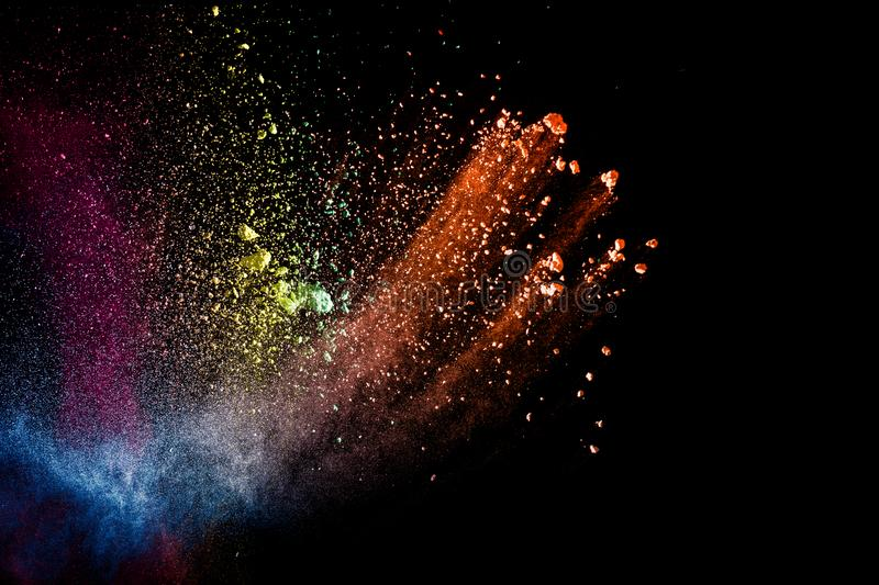 Abstract colorful dust particles textured background.Multicolored powder explosion on black background stock photography
