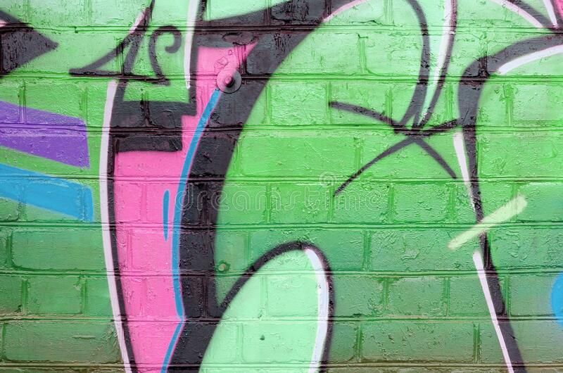 Abstract colorful fragment of graffiti paintings on old brick wall in green colors. Street art composition with parts of unwritten royalty free stock photography