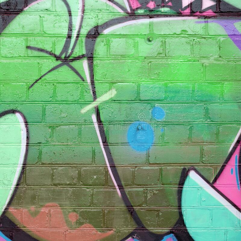 Abstract colorful fragment of graffiti paintings on old brick wall in green colors. Street art composition with parts of unwritten royalty free stock image