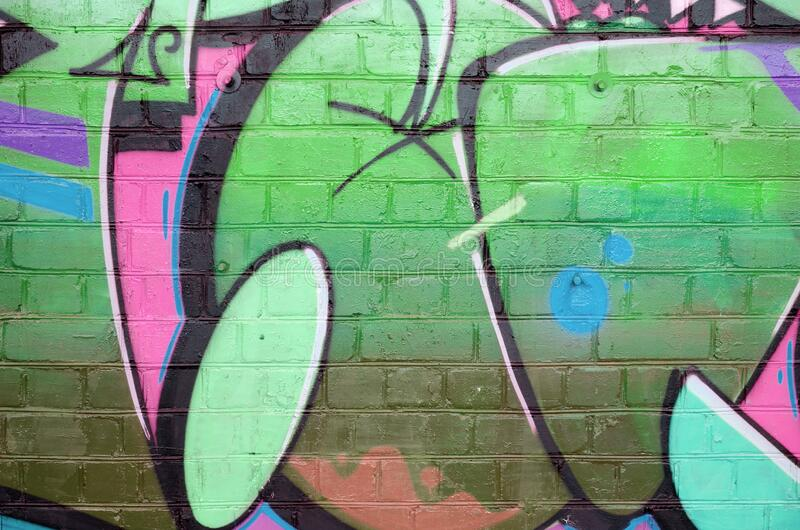Abstract colorful fragment of graffiti paintings on old brick wall in pink and green colors. Street art composition with parts of stock image