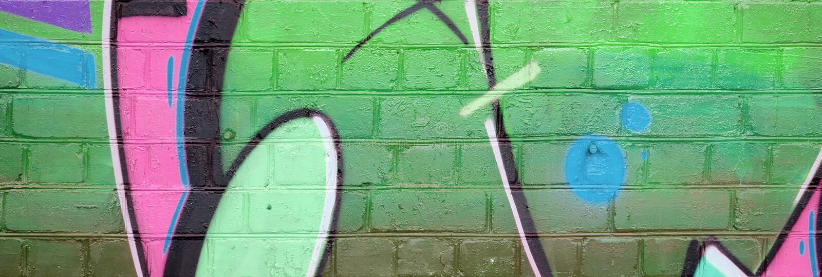 Abstract colorful fragment of graffiti paintings on old brick wall in pink and green colors. Street art composition with parts of stock photography