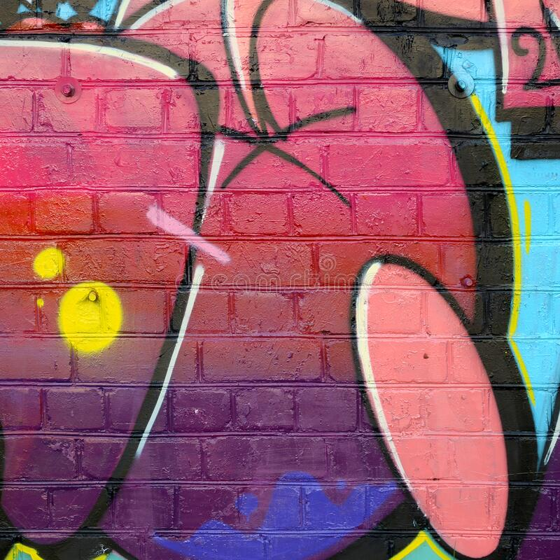 Abstract colorful fragment of graffiti paintings on old brick wall. Street art composition with parts of unwritten letters and royalty free stock photography