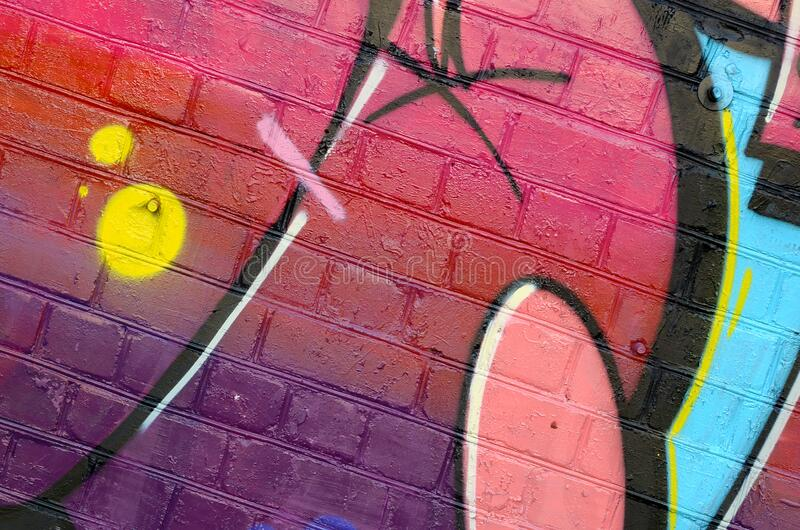 Abstract colorful fragment of graffiti paintings on old brick wall. Street-art composition with parts of wild letters and stock photography