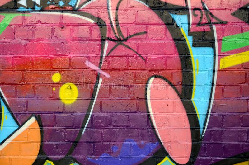 Abstract colorful fragment of graffiti paintings on old brick wall. Street-art composition with parts of wild letters and royalty free stock photography