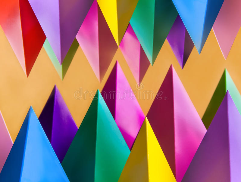 Abstract colorful geometric pattern with prism pyramid triangle shape figures. Yellow blue pink green violet red colored. Objects royalty free stock photo
