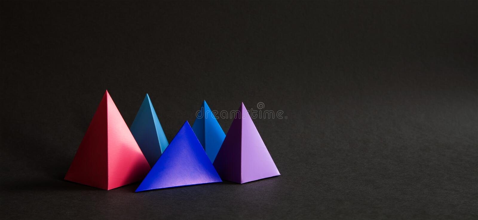 Abstract colorful geometrical composition. Three-dimensional prism pyramid objects on black paper background. Pink blue stock photography