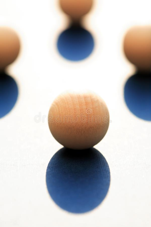 Wooden Balls With Shadow. Abstract composition with few small wooden balls on light background stock image
