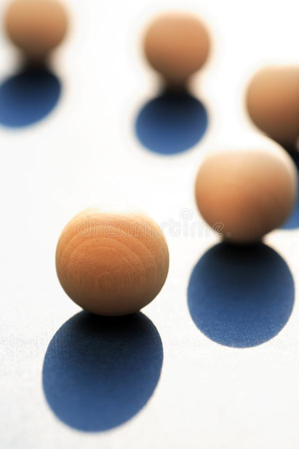 Wooden Balls With Shadow. Abstract composition with few small wooden balls on light background royalty free stock photo
