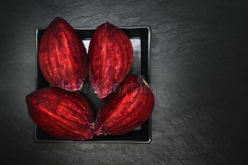 Abstract composition of four pieces chopped beetroot placed on black plate and black stone background.  royalty free stock photos