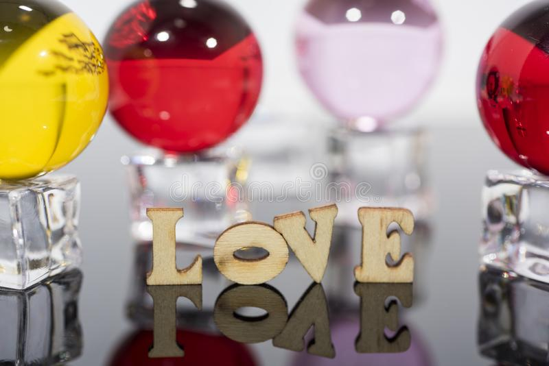 Abstract composition of love. Isolated wooden letters and glass balls stock images