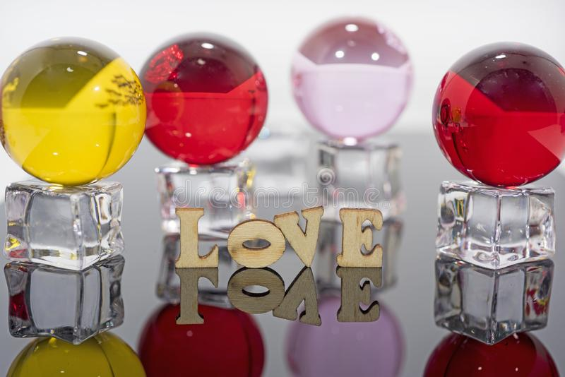 Abstract composition of love. Isolated wooden letters and glass balls royalty free stock image