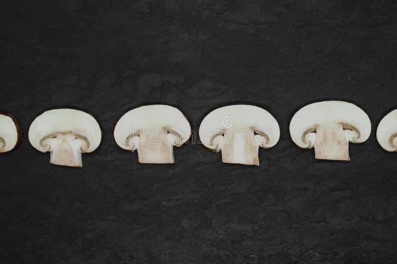 Abstract composition of split up brown champignons mushrooms placed in line on stone background surface stock photo