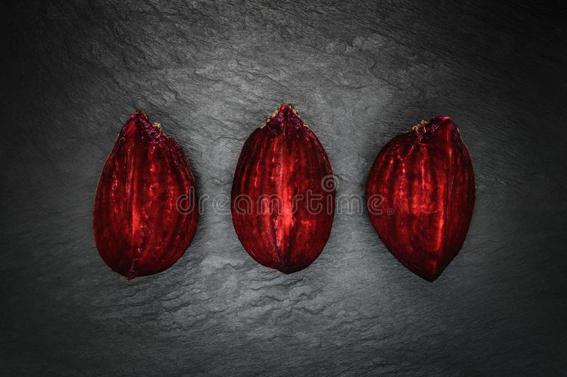 Abstract composition of three pieces beetroot placed in line on black stone background surface royalty free stock photography