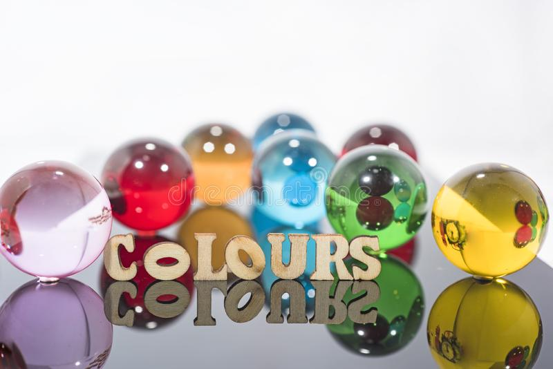 Abstract composition with transparent glass balls and wooden letters royalty free stock photos