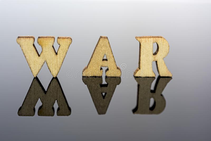 Abstract composition of war. Isolated wooden letters and red glass ball stock photography