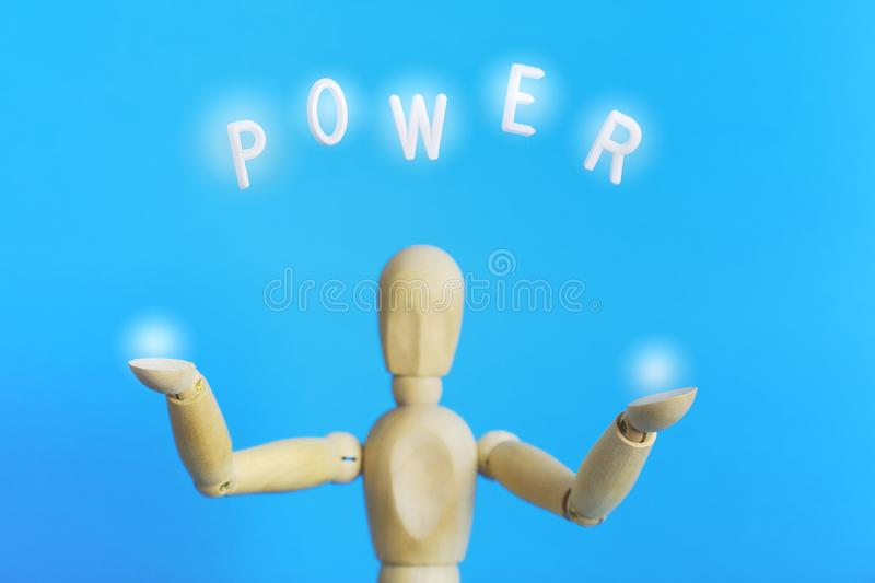 Abstract concept of power. Wooden character holding light  globes in the hands. Creative concept of powerful character on light blue background holding light in royalty free stock image