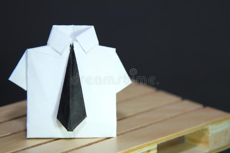 Abstract concept of white collar worker with origami suit and black tie. Wooden and black background stock images