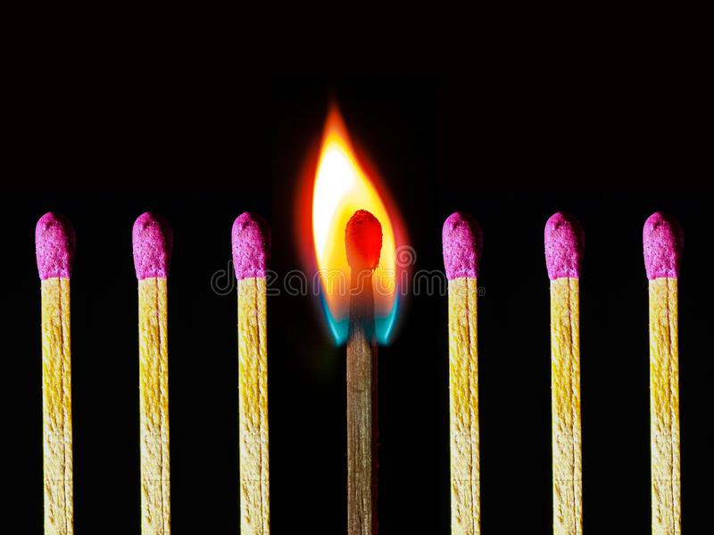 Abstract photo of burning matchstick together with other not burnt matchsticks royalty free stock image