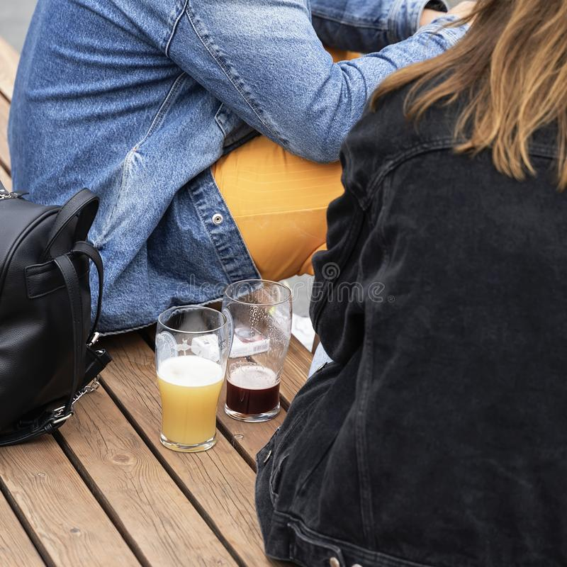 Abstract couple, a guy and a girl sitting drinking fresh dark and light beer stock photo