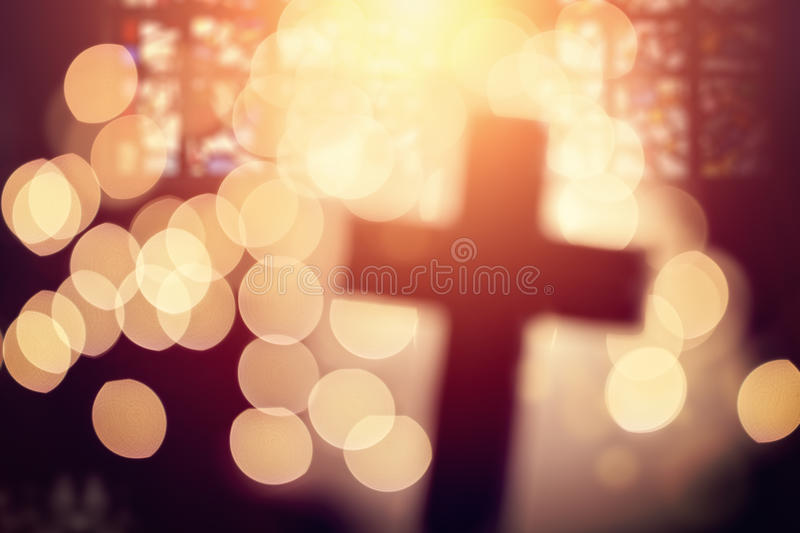 Abstract cross in church interior. Abstract defocussed cross silhouette in church interior against stained glass window concept for religion and prayer royalty free stock photography