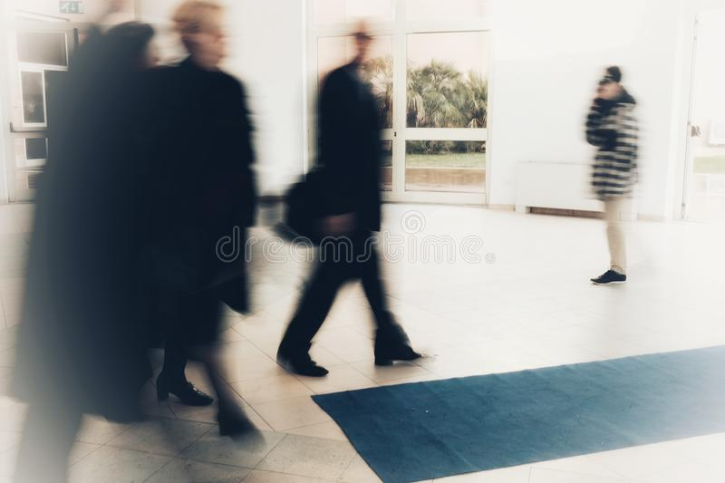 Abstract crowd of anonymous blurred people walking in shopping mall royalty free stock photo